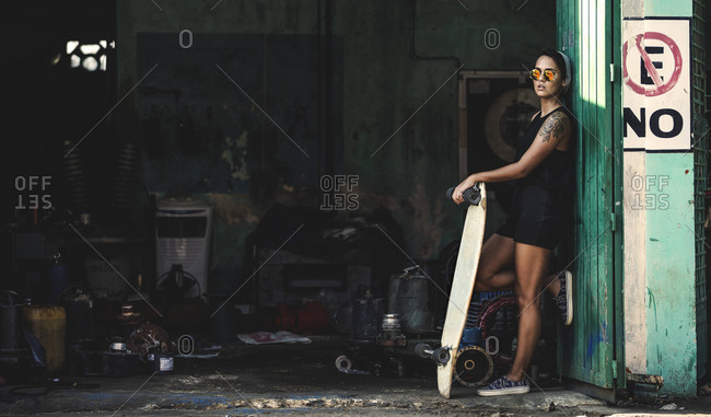Young woman standing with skateboard in doorway of garage full of junk