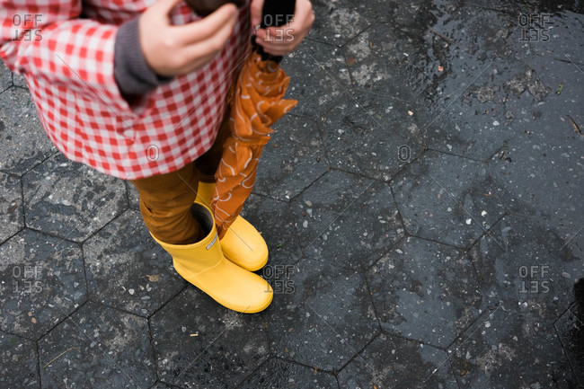 Girl with rain gear standing on pavement
