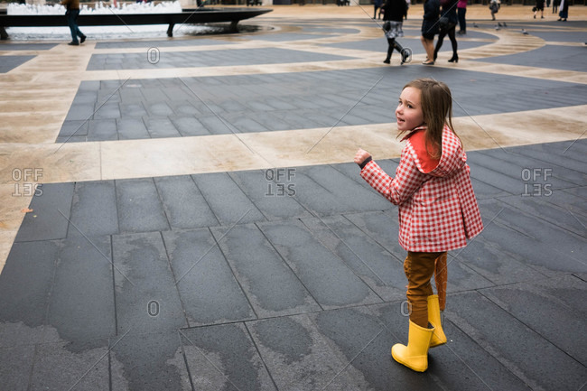 Girl in rain clothing standing in city square
