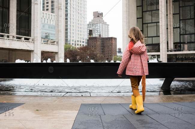Girl in rain clothing standing by fountain