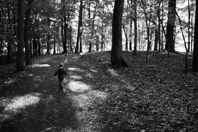 Girl and boy walking down trail in woods