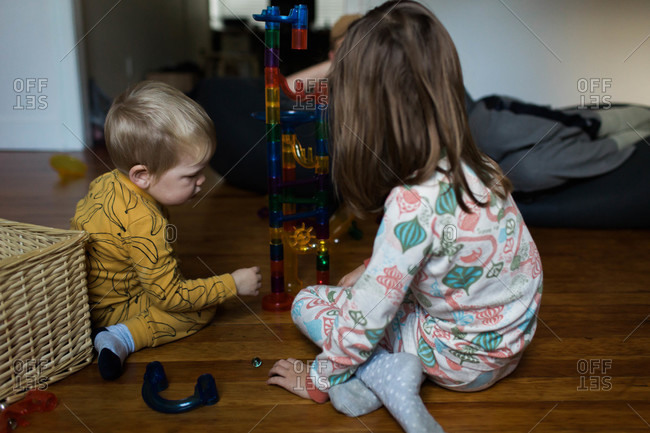 Boy and girl playing with stacking chute toy
