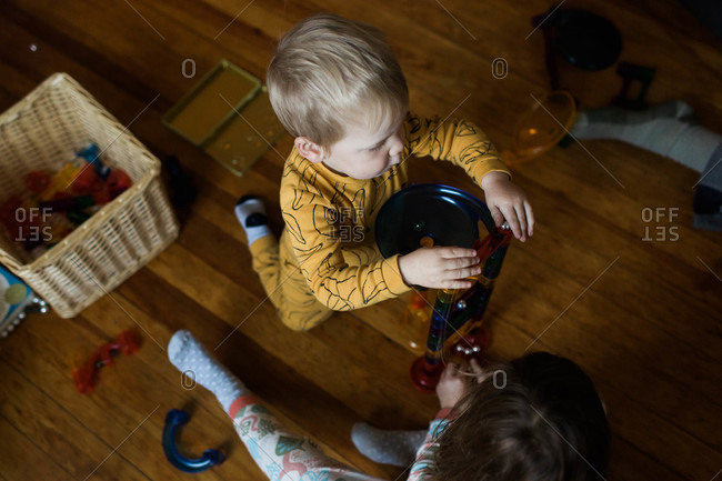Boy and girl playing with a stacking chute toy