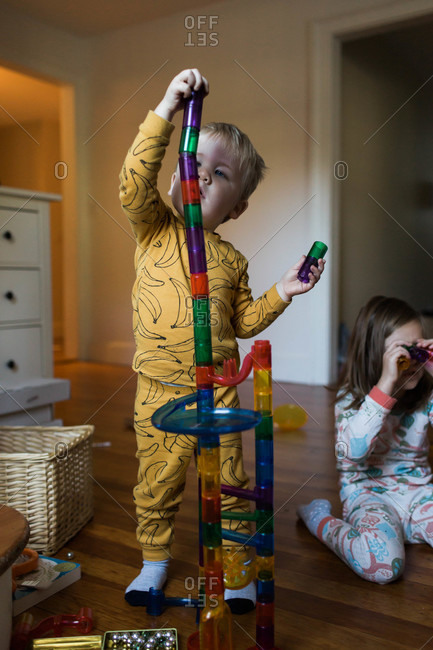 Toddler boy building up a chute toy