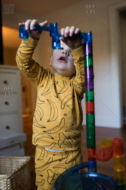 Toddler boy stacking up a chute toy