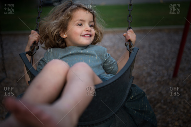 Little girl swinging on a park swing