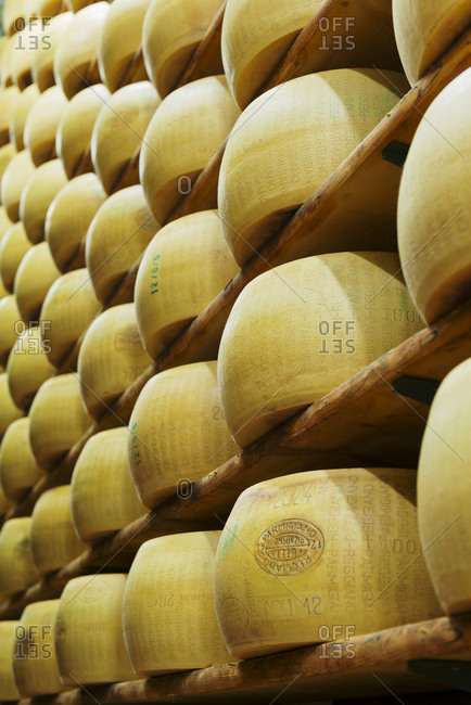 Modena, Italy - October 23, 2013: Parmesan cheese wheels aging on shelves