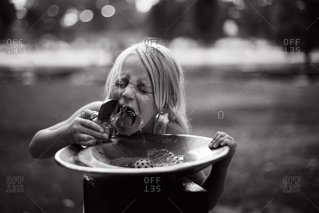 Girl drinking from a public water fountain