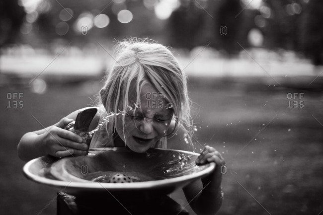 Girl at a public water fountain