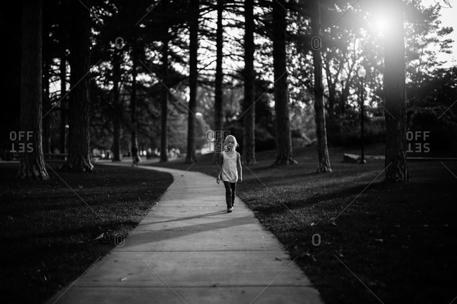 Girl walking on a sidewalk in a park
