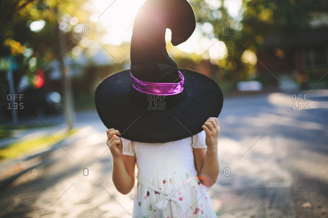 Girl holding a witch's hat over her head
