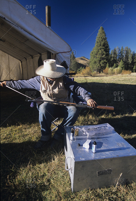 Cowboy cleaning his rifle in Smoky Mountains, Idaho