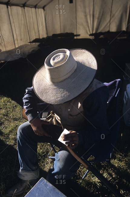 Cowboy cleaning his rifle in the Smoky Mountains of Idaho