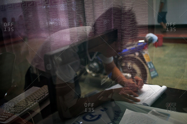 Man signs for medical procedure in Chinese office