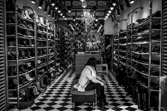 Jiangxi province, China - December 13, 2013: Woman sitting in a shoe shop in China