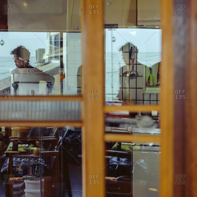 Hamagurihama, Japan - 2014: Man reflected in windows of Japanese caf_