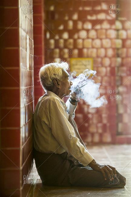 Mandalay, Myanmar - September 27, 2015: Elderly man smoking at a temple