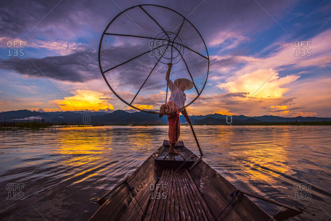 Inle Lake, Myanmar - October 1, 2015: Man fishing with a net from a canoe