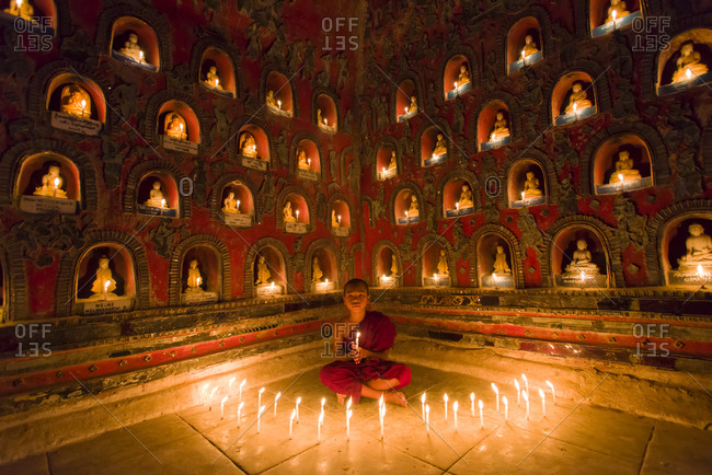Myanmar - October 3, 2015: Child monk in meditation with candles at a temple