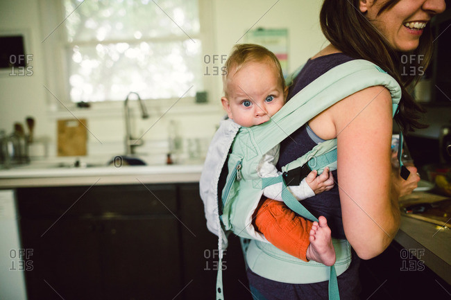 Mother holding baby in back pack style baby carrier