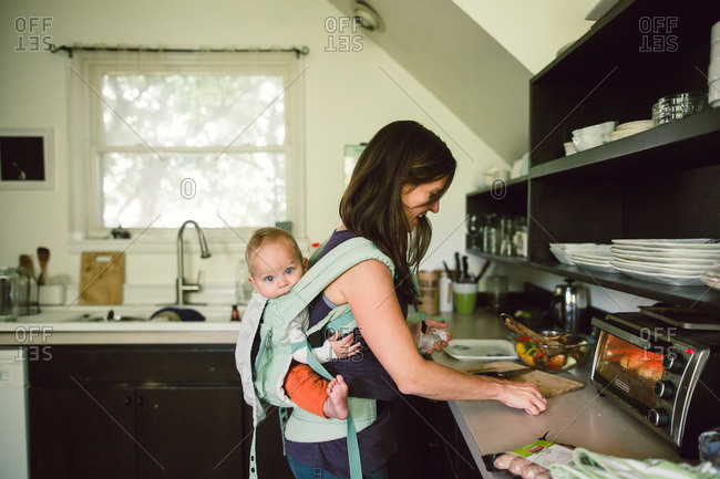 Mother holding baby in back pack style baby carrier as she prepares a meal