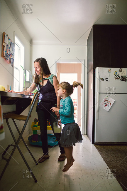 Mother holding baby in back pack style baby carrier as she writes a note