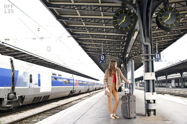 Young woman with luggage on train platform
