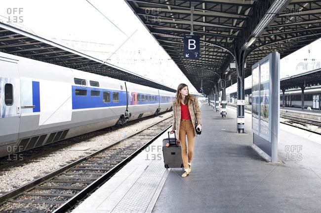 Woman walking with luggage on train platform