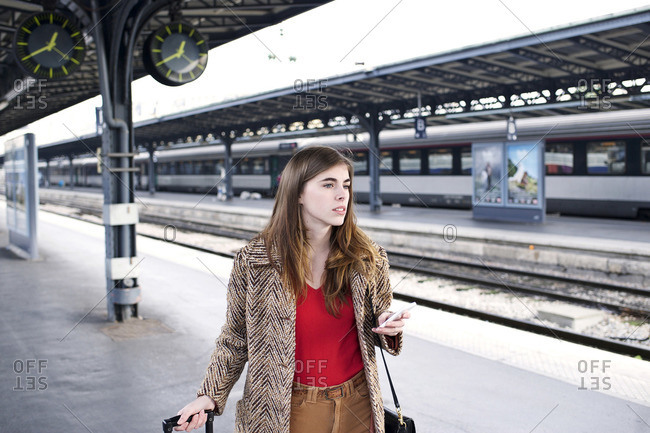 Woman with smartphone on train station platform