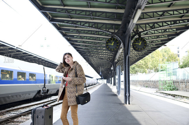Woman waiting with luggage on train station platform