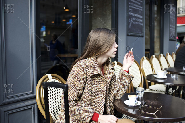 Woman with luggage smoking at outdoor cafe