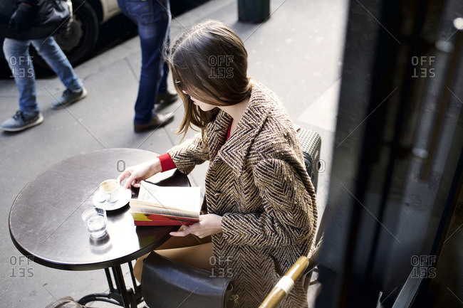 Woman in coat reading book at outdoor cafe