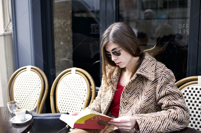 Woman in a coat reading at outdoor cafe