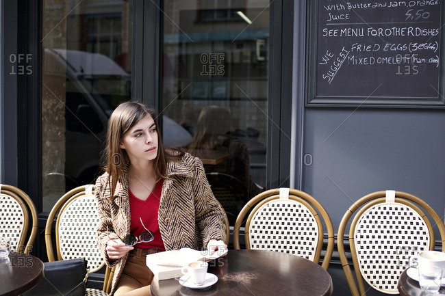 Woman staring down sidewalk at outdoor cafe
