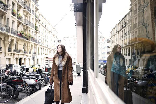 Stylish woman strolling on Parisian sidewalk