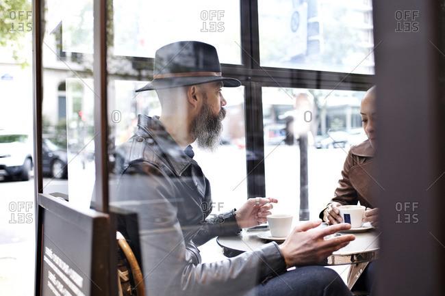 Man with long beard talking at cafe