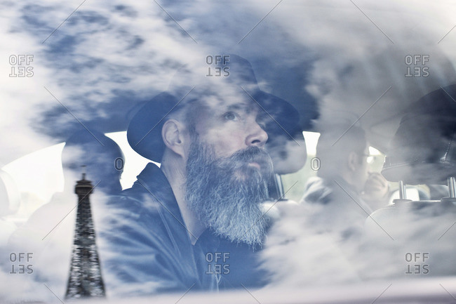 Bearded man staring at Eiffel Tower in cab