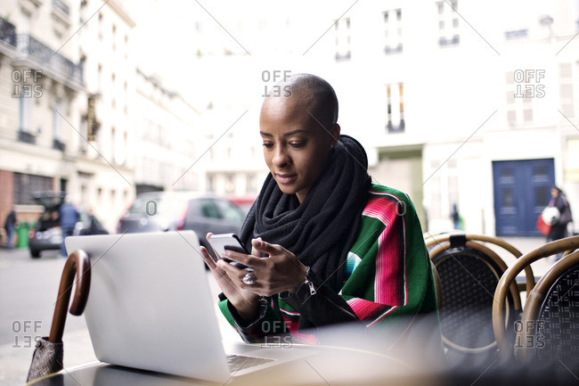 Woman at cafe in poncho with devices