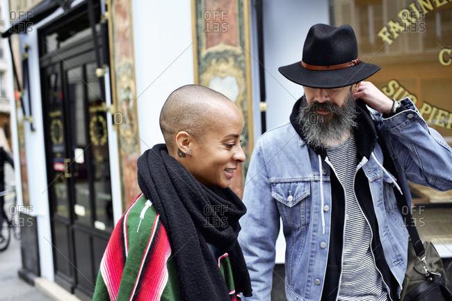 Multi-ethnic couple walking down city street