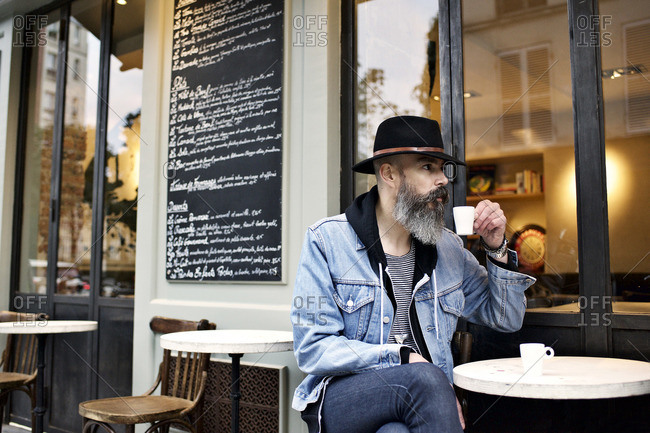 Man with long beard sitting outside cafe