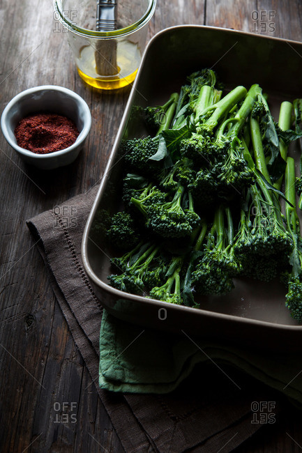 Broccolini in a roasting pan with olive oil and spices