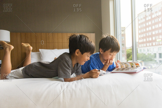 Young asian boys looking at comic book in hotel bed