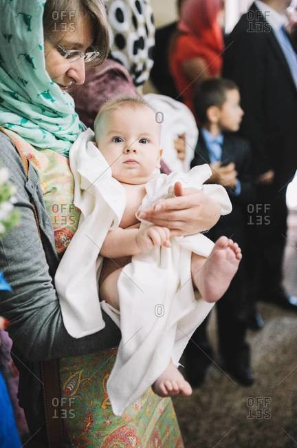 Baby boy held by his godmother during an Orthodox Christian Baptism in Chisinau, Moldova