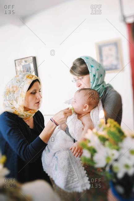 Godmother holding boy during Orthodox Christian Baptism while his mother gives him a pacifier in Chisinau, Moldova