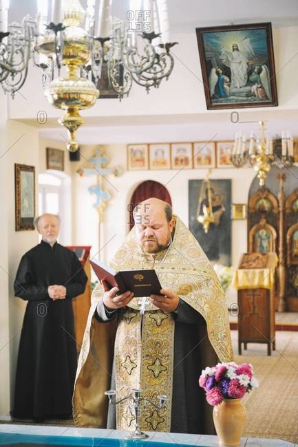 Chisinau, Moldova - September 09, 2013: Priest reading from Bible during religious event in Russian Orthodox Church
