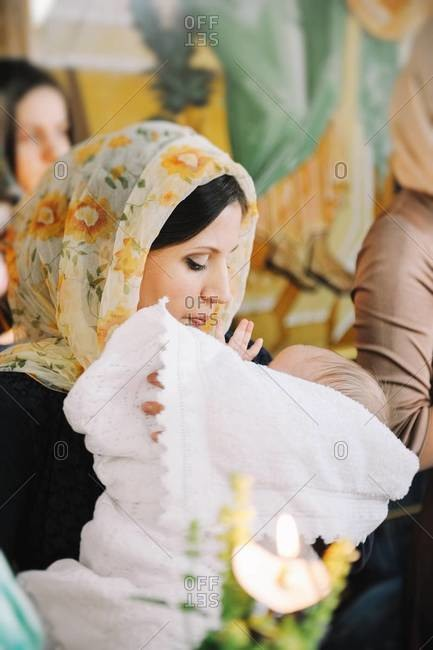 Mother with baby boy after Orthodox Christian Baptism in Chisinau, Moldova