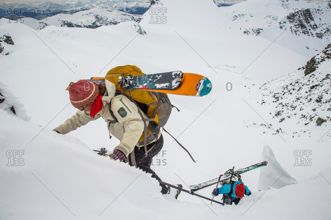 Skiers boot pack with gear on their back up a steep slope to a notch in the Coast Mountains during the Spearhead Traverse in Whistler, British Columbia, Canada