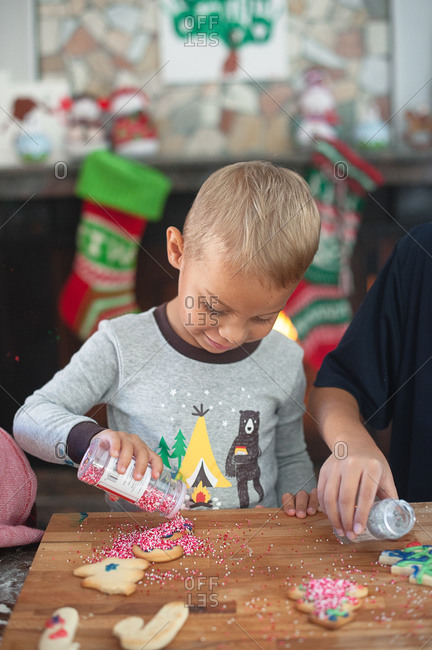 Boy dumping sprinkles on a Christmas cookie
