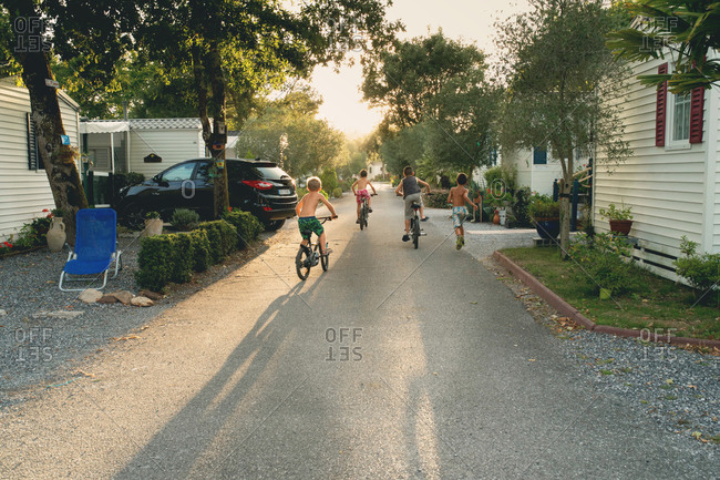 Three children riding bikes and one child running