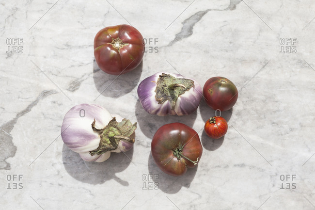 Tomatoes and eggplants on a marble background